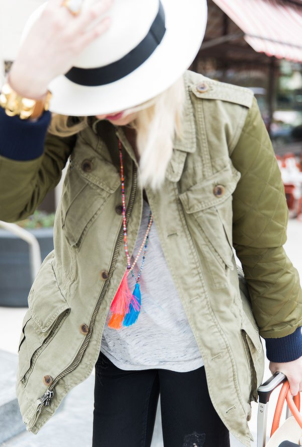 The best airport outfit: military jacket, panama hat, tassel necklaces