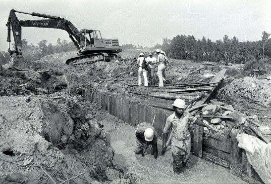 Photograph of workers on old wooden dam on Neuse River.