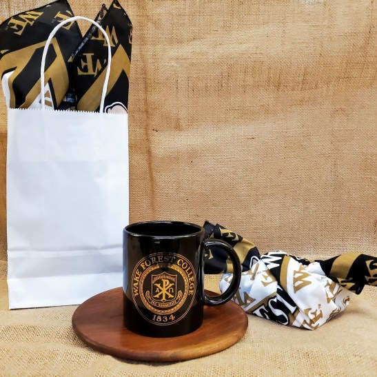 Black mug with gold printing on a wooden saucer. Gift bag and box wrapped with cloth bandana.