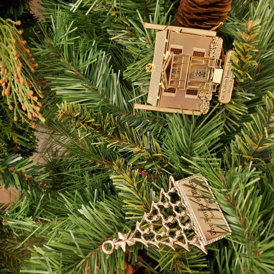 Photograph of two ornaments on green garland.