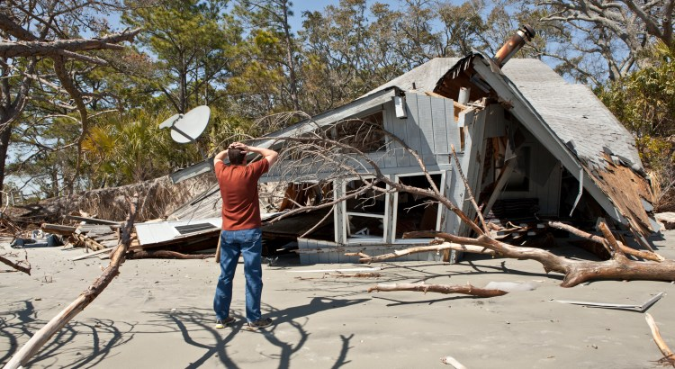 man grieving over house destroyed in flood.
