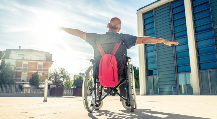 Invalid man sitting on a wheel chair and enjoying a walk outdoors