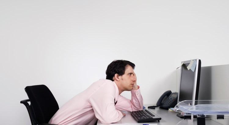 Side view of a bored male office worker looking at notes on computer monitor at desk