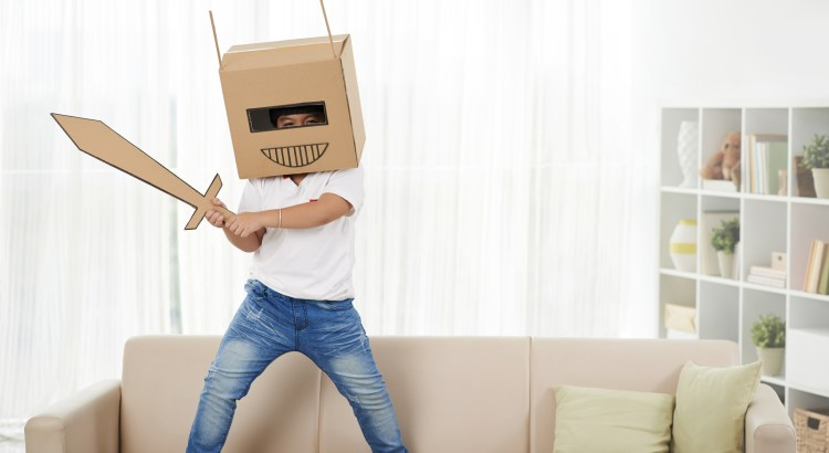 Cheerful child playing in robot at home