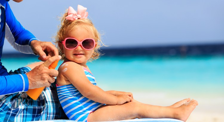 father applying sunblock cream on daughters shoulder, sun protection