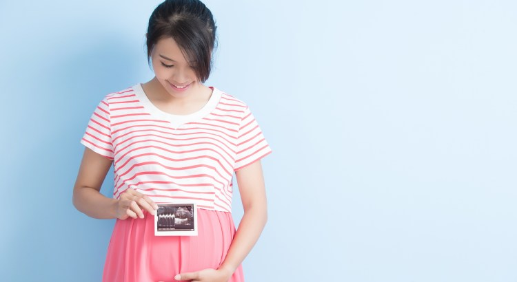pregnant woman take ultrasound picture and smile isolated on bluebackground, asian