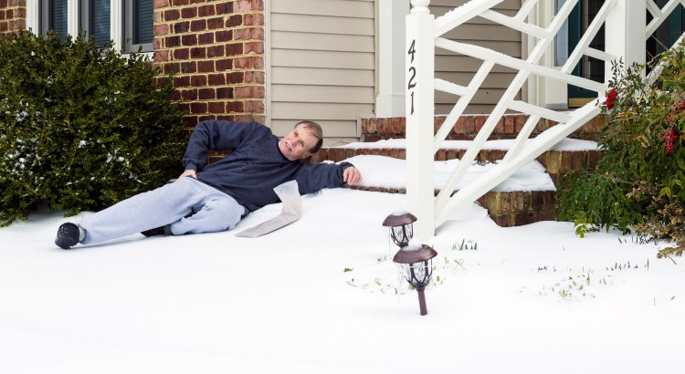 An adult male retrieving a news paper slips and falls on icy steps.