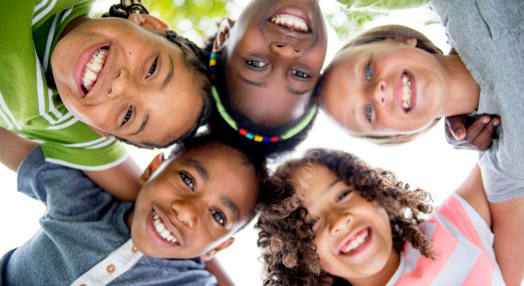 A multi-ethnic group of elementary age children are huddled together, standing in a circle with their heads in the center looking down at the camera. They are smiling and looking at the camera.