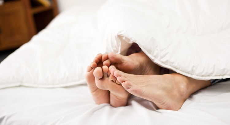 Mature couple showing feet from under the covers.