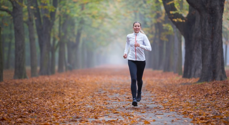 43 year old woman jogging in alley autumn fog exercising series with white jacket full body portrait front shot with shallow focus depth and blurred background