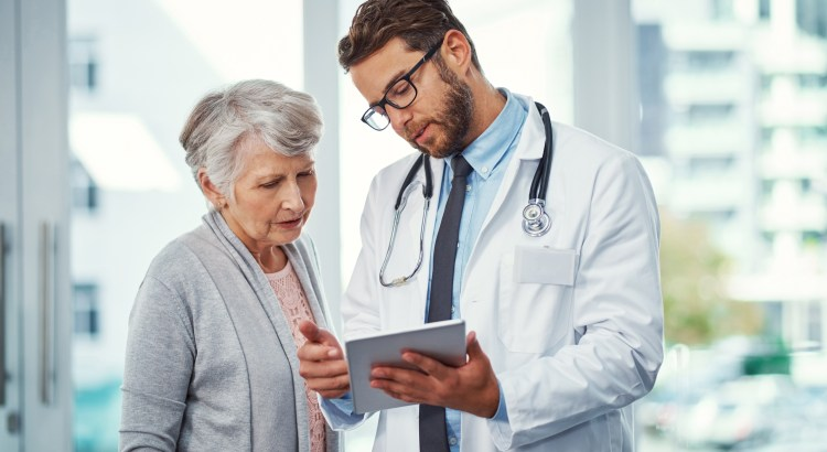 Shot of a doctor discussing something on a digital tablet with a senior patient in a clinic
