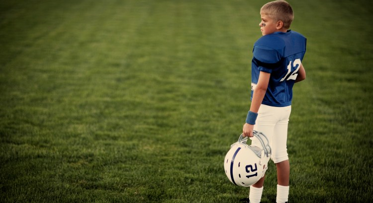 A young American boy dreams of throwing touchdowns on the football field.
