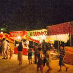 お祭りの屋台と子供たちの画像