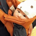 赤ちゃんがオレンジ色の抱っこひもで抱っこされている画像
