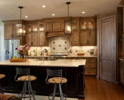 kitchen,island,two toned cabinets,decorative details,tile backsplash,hanging light fixtures