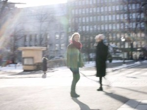 A Walker on the street watching towards the camera. Another blurry figure in the background walking to another direction. Sun stripes and movement making the image a bit unclear.