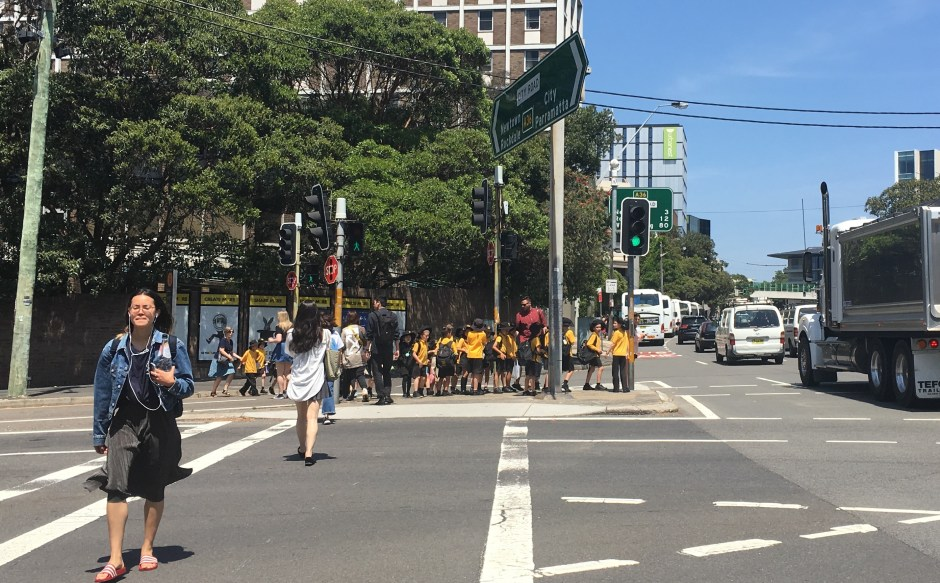 At least 20 people, most of them children, queued up like bowling pins, on a refugee island at City Road and Cleveland Street, Sydney. Other groups are held back at the Seymour Centre, or have been already ferried across City Road to Victoria Park. This is typical, but not good, urban design.