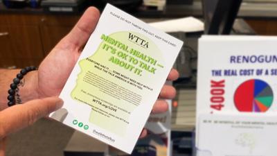 Firearm salesman handing WTTA mental health flyer to customer