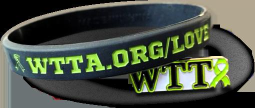 """Rubber wristband with """"WTTA.org/love"""" printed on it alongside a WTTA enamel pin"""