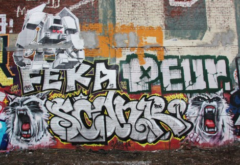 letters by Scaner (bottom) between hissing cats by Axe, Feka and Peur (middle) and wheatpaste by Lovebot (top), by train tracks.