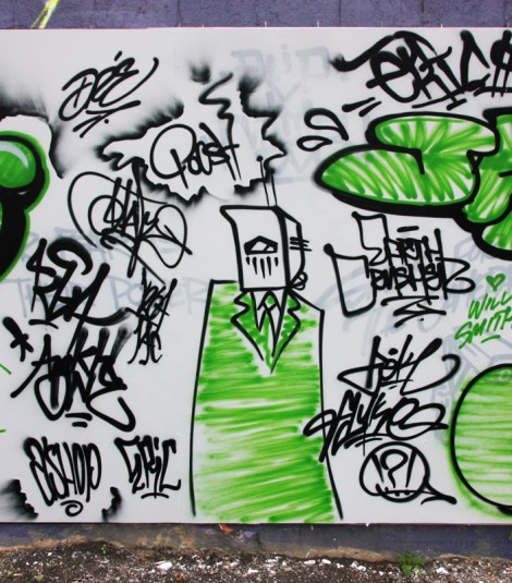 Earth Crusher character on a temporary A'Shop wall, surrounded by tags from both Earth Crusher and Dré, as well as Zek, Fluke, Ankh One, etc.