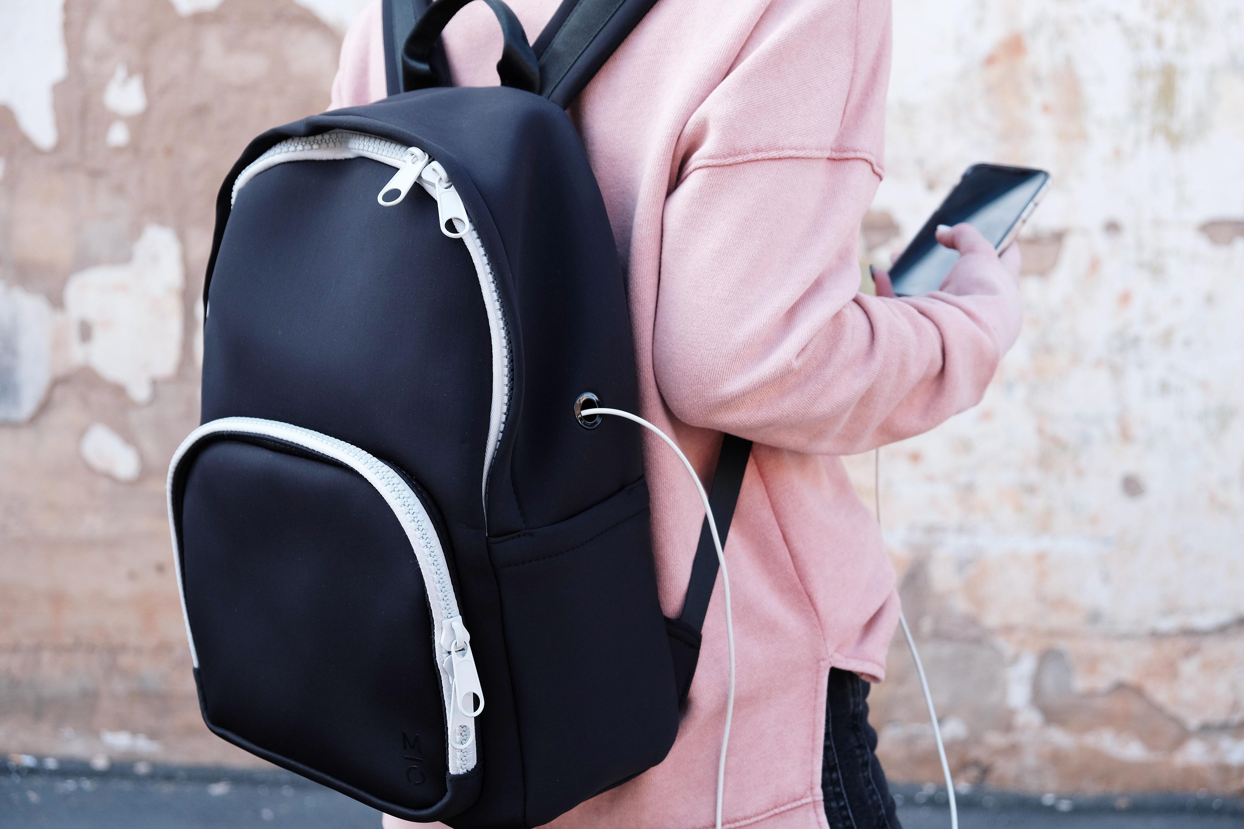 woman wearing black neoprene backpack with wireless charging bank