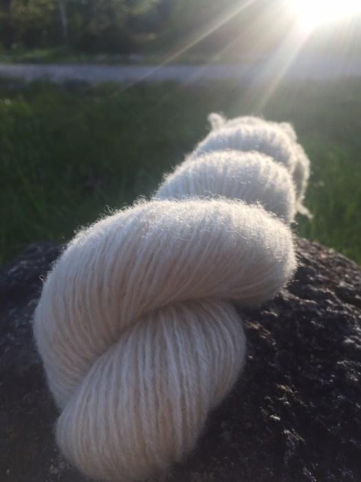 A skein of handspun white yarn in backlight