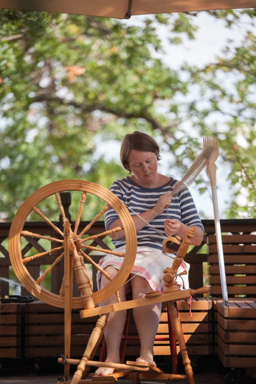 Josefin Waltin spinning flax on a spinning wheel on the balcony.