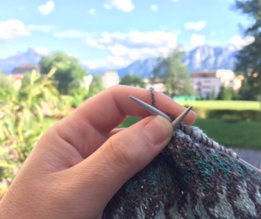 Close-up of stranded knitting. Mountains in the background.