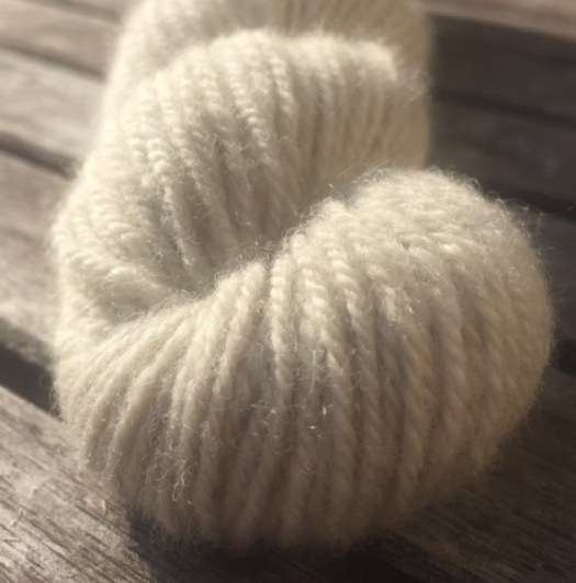 Close-up of a skein of white handspun yarn.