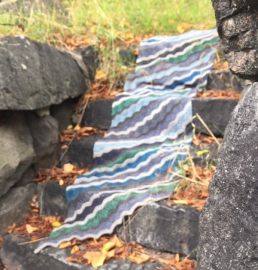 A striped shawl draped over stone steps