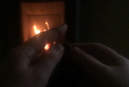 A dark picture of two hands knitting in front of a fireplace