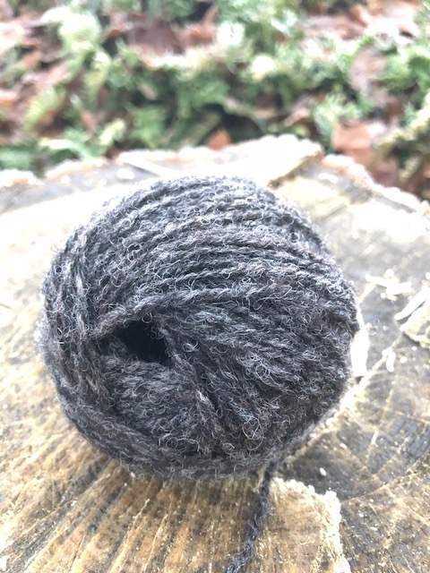 a hand wound ball of dark grey yarn