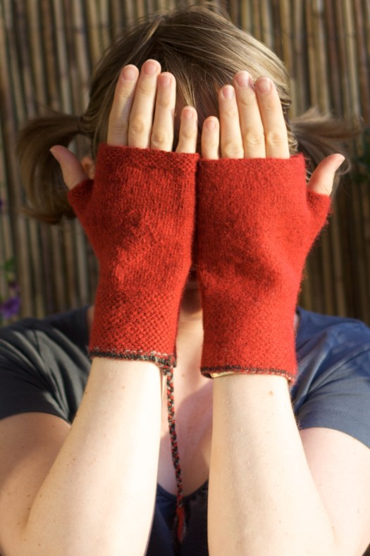 A person wearing a pair of red half-mitts