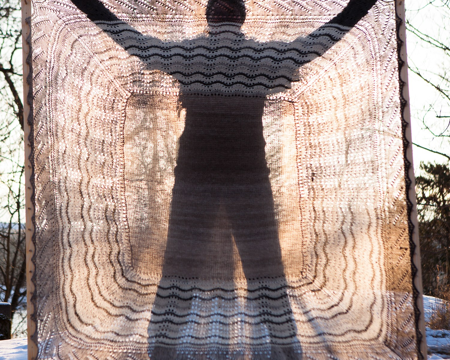 A person standing behind a stretched Shetland Hap