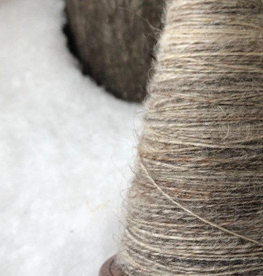 A close-up of a spindle with grey yarn