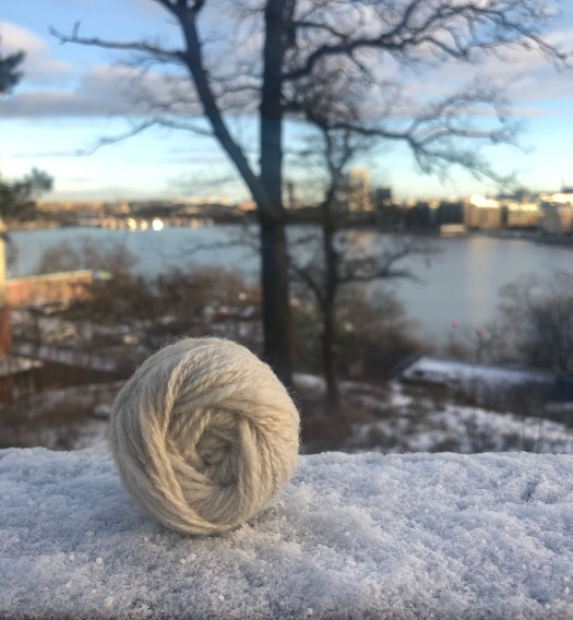 A hand wound ball of handspun yarn. A winter city in the background