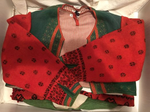 A jacket with a woven green bodice and sewn on twined knitted sleeves in red.
