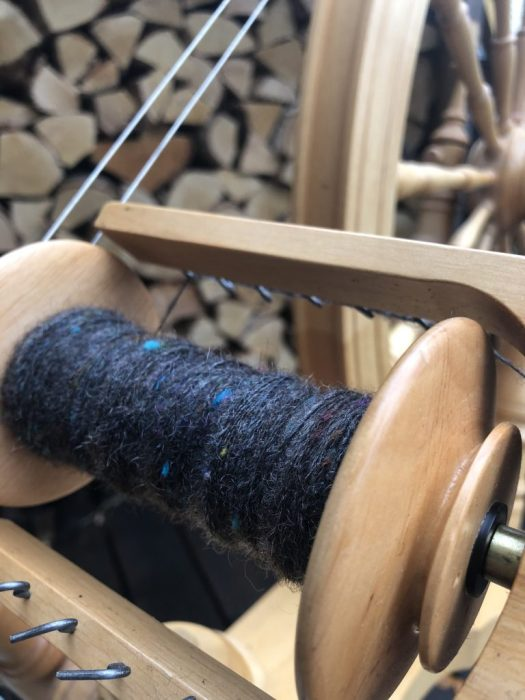 A bobbin with dark grey yarn with specks of colour