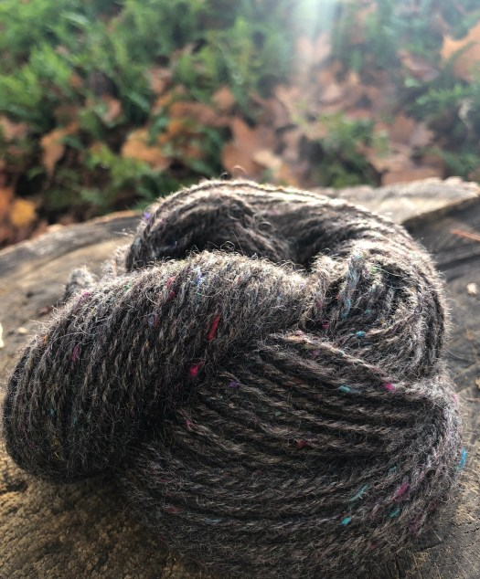 A sken of dark grey yarn with colored specks in it