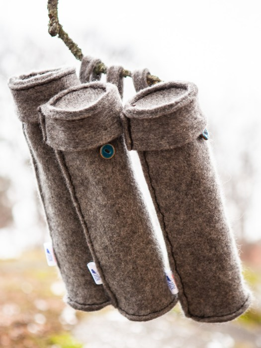 Three woolen spindle cases hanging on a tree branch.