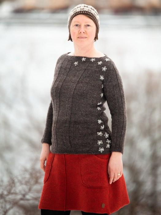 Josefin Waltin wearing a dark grey sweater with embroidered flowers