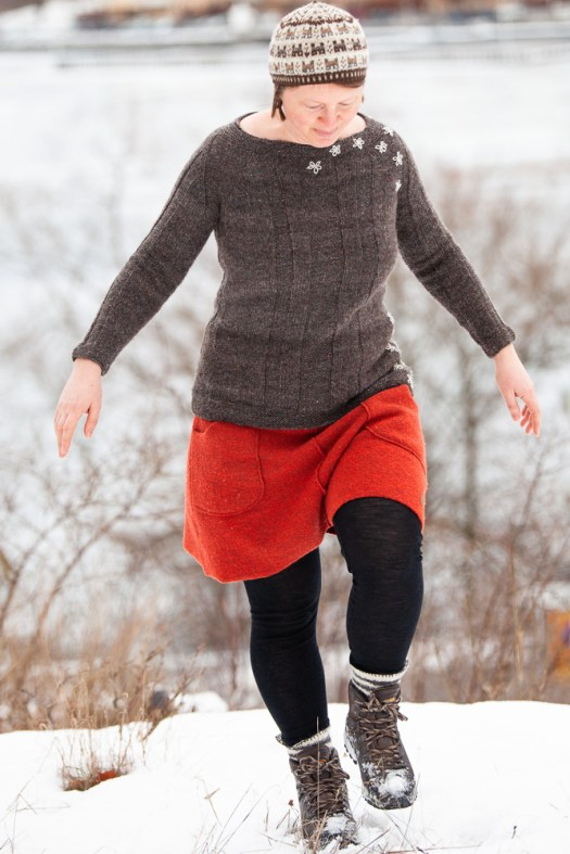 Josefin Waltin walking in the snow, wearing a dark grey sweater with embroidered flowers.