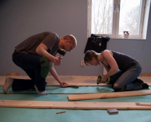 A man and a woman putting together a wooden floor
