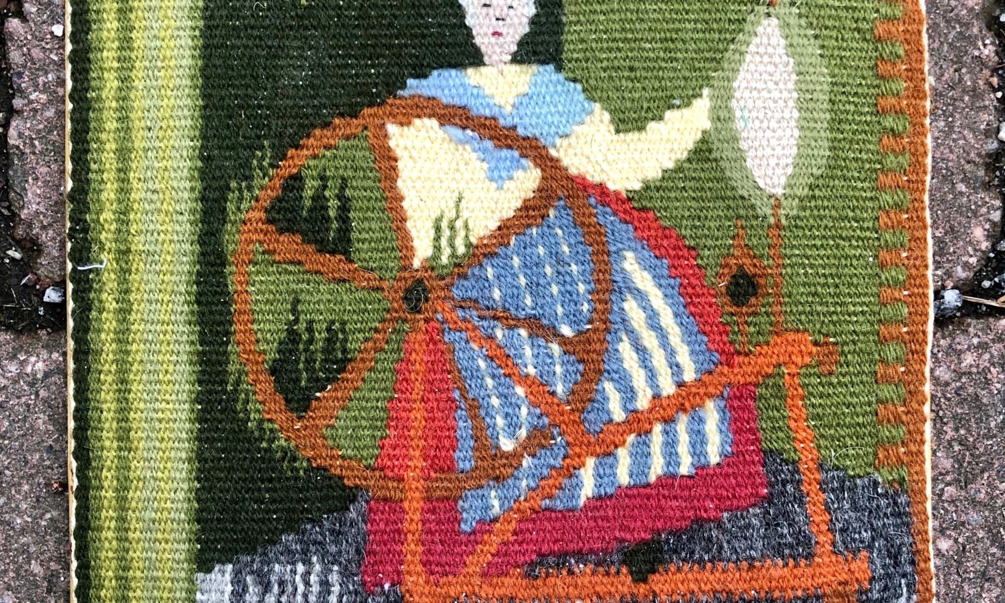 Flemish tapestry weave with a woman spinning on a spinning wheel.