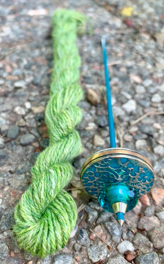 A small turquoise spindle with silver decorations and a small skein of green yarn.