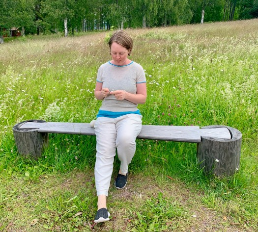 A woman knitting on a bench. A meadow in the background.