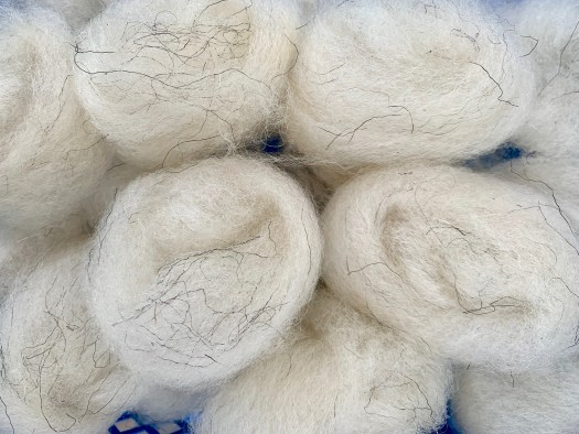 Balls of combed light grey wool. Some coarse fibers are in the balls.