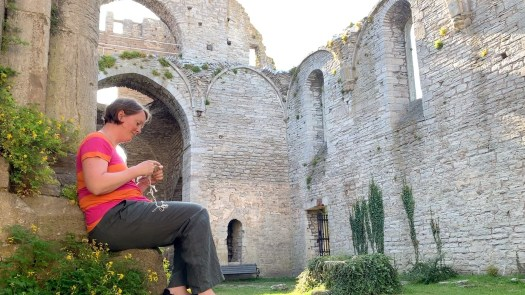 A woman knitting in a ruin. There is no roof in the ruin.