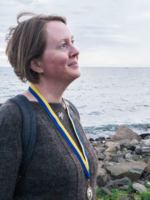 A woman standing by the sea. She is wearing a knitted sweater and a medal around her neck.
